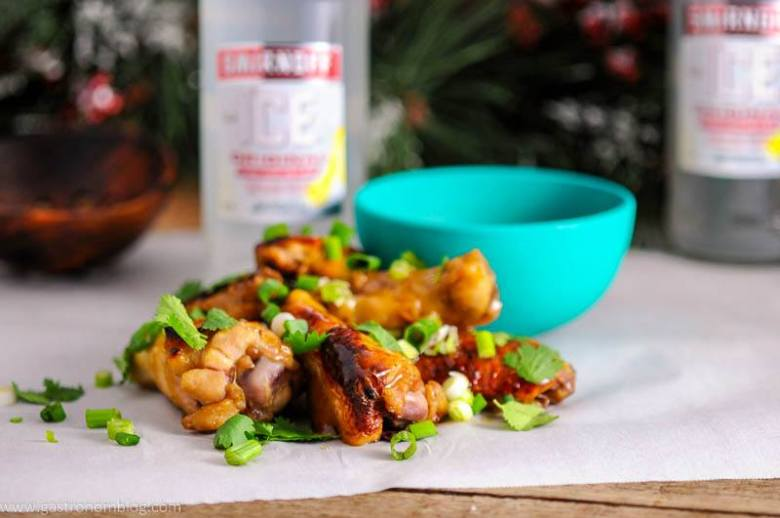 Citrus Asian Chicken Wings with green onion and cilantro on parchment paper. Green bowl with dipping sauce and Smirnoff bottle in background