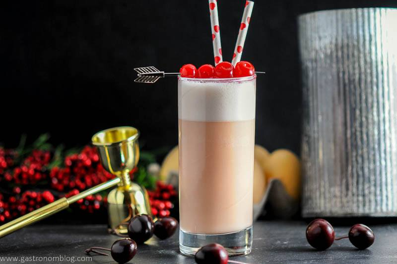 A highball glass with a Cherry Toasted Cream Ramos Gin Fizz , double jigger and fresh cherries