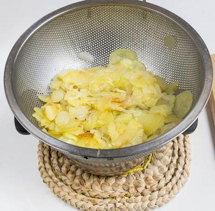 Escurriendo las patatas, calabacín y cebolla