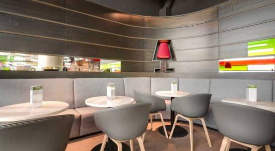 Gemütlich: gepolsterte Bänke mit runden Kaffeehaustischen aus weißem Marmor