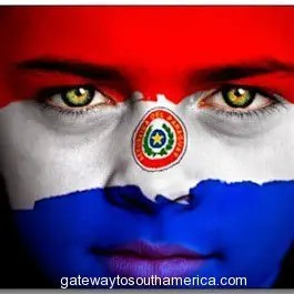 Portrait of a boy with the flag of Paraguay painted on his face.