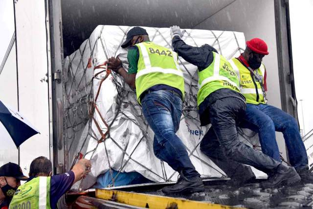 Workers load South Africa's first Covid-19 vaccine doses at OR Tambo airport in Johannesburg on Feb. 1.