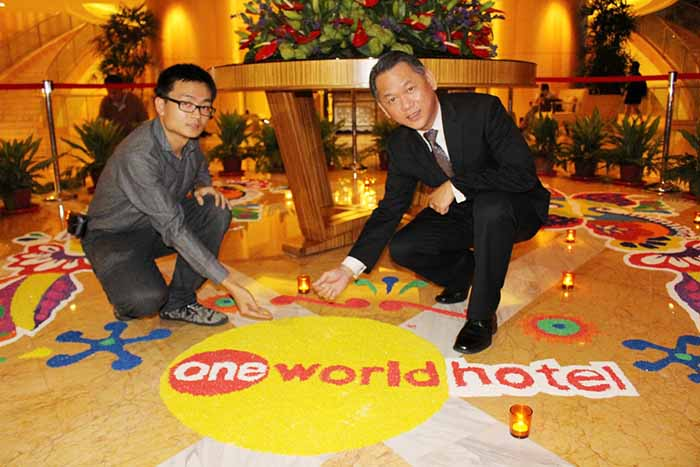 Mr. Steven Chong from Saito College and One World Hotel's General Manager, Mr. Ho Hoy Sum putting the final touch to the artwork together.