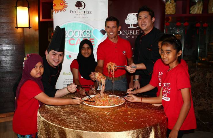 McEwen (third from left) tossing yee sang with children during charity lunch at DoubleTree by Hilton Kuala Lumpur