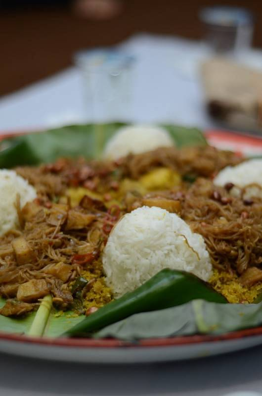 Delicious Nasi Ambeng and side dishes placed together in a platter meant to be shared among four or five persons
