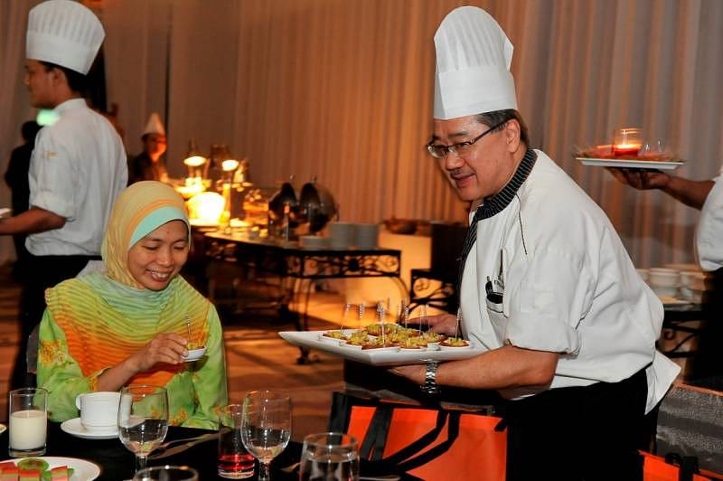 Executive Chef Keong of THE CHEFS programme presenting his specialty cuisine to Ms Hidayah from Ericsson
