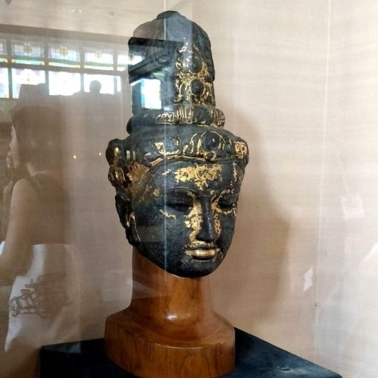 A sculpture of a deity's head made from bronze and coated with gold at Sonobudoyo Heritage Museum.