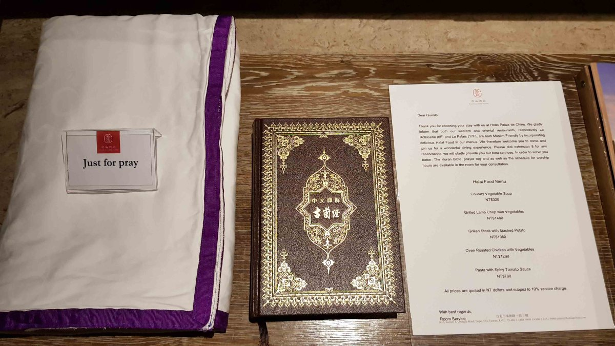 A copy of Al Quran with praying mat and halal menu inside the room.