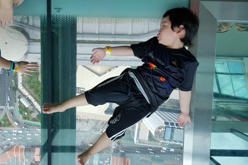 Child lying on see-through bottom-glassed ledge at The Top Penang on level 65