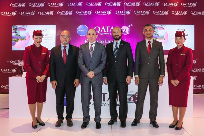 Qatar Airways Senior Vice President Asia Pacific, Mr Marwan Koleilat, Qatar Airways Group Chief Executive, His Excellency Mr. Akbar Al Baker, Chief Minister of the State of Kedah, Dato' Seri Mukhriz Tun Mahathir, Chief Executive Officer of Langkawi Development Authority (LADA), Dr. Hezri Bin Adnan, flanked by two Qatar Airways flight crew members.