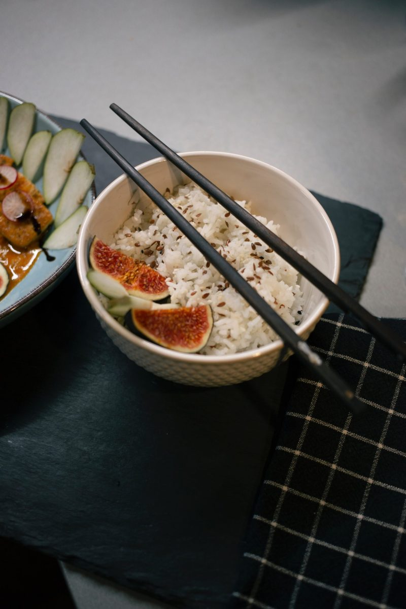 Uncrossed stainless steel chopstick on white ceramic bowl