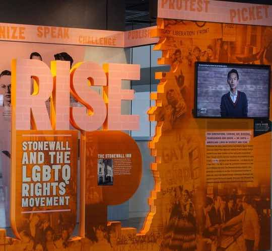 Photo of Rise Up exhibit pieces in orange and tv screen on wall