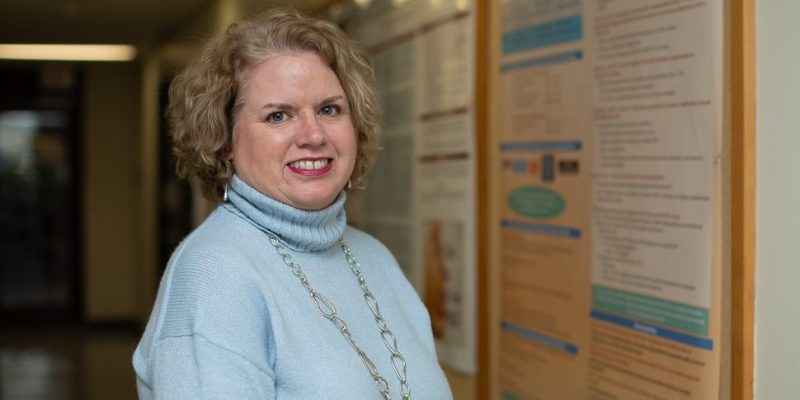 Faculty of Nursing professor, Dr. Anne Kearney, stands next to one of her research poster about mammography screening