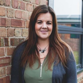 Danni Young works at GB Finance, a recruitment agency in Gloucestershire. Danni leans against a brick wall, smiling, wearing a green shirt and grey cardigan