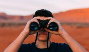man with binoculars in desert
