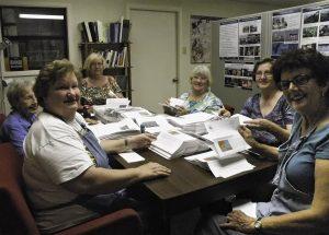 smiling volunteers at a table help prepare mailings