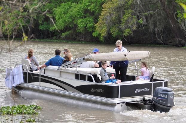 people enjoy a pontoon boat ride on the bayou