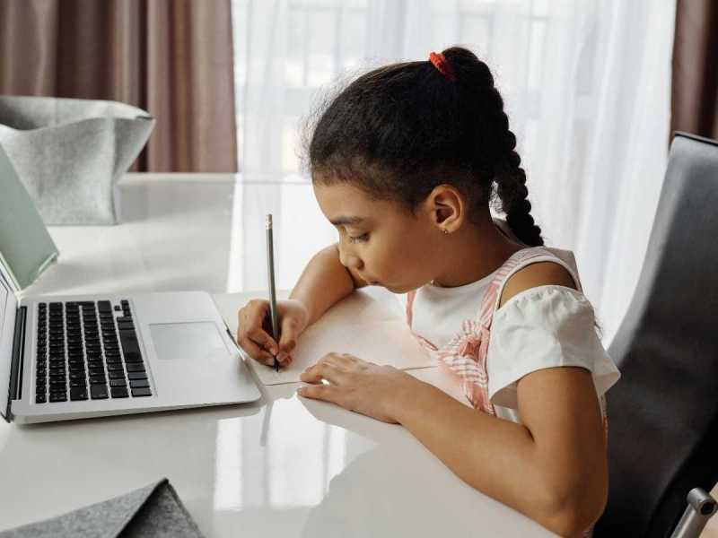 Child writing while working on laptop
