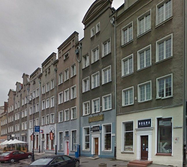 Fragment Ul Szerokiej zbudowany w latach 1952-56. Linia zabudowy i szerokość działek nie odpowiadają pierwotnej. Tylko nałożone na blok szczyty sugerują historyzującą zabudowę.