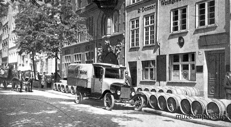 Fragment ulicy Ogarnej (Hundegasse) – na pierwszym planie kamienice nr 81–82 z beczkami i samochodem firmy winiarskiej R. Denzera. Obecnie znajdują się w tym miejscu smutne imitacje dawnych kamienic. (Ok. 1920) www.muzeumpolski.pl