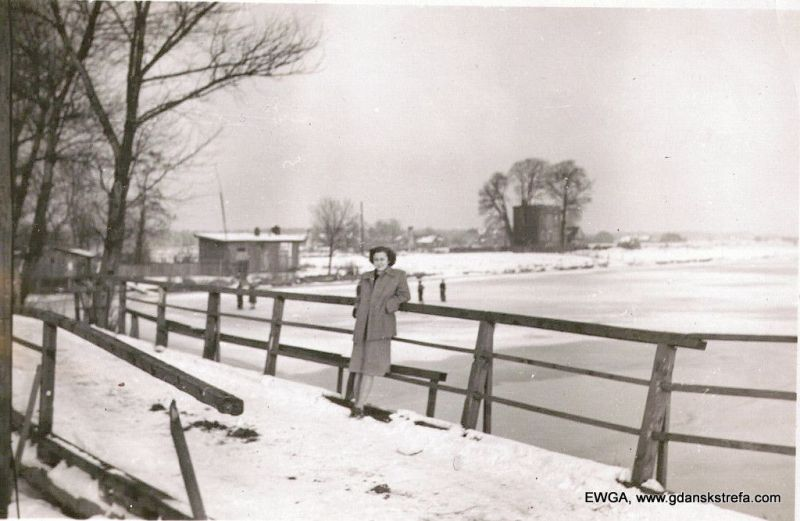 Mostek na Krakwiecką Kępę, połowa lat 50. Na mostku mama właścicielki zdjęcia. Widać piętrowy, murowany dom rodzinny pana Antoniego Benka (naszego czytelnika) na cyplu wyspy.