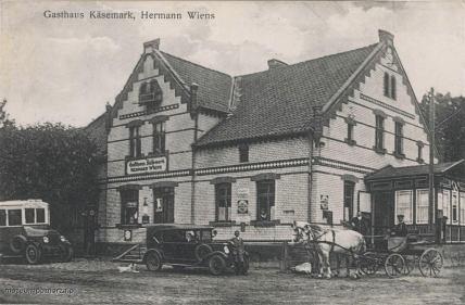 Gospoda Hermana Wiensa w Kiezmarku. Na budynku liczne szyldy reklamowe.Widoczny dystrybutor paliwa i autobus.