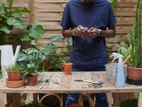 Young man using smartphone on his terrace while gardening model released Symbolfoto property released PUBLICATIONxINxGER