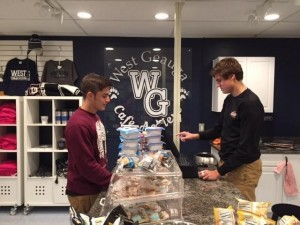 Submitted West Geauga High School student Jesse Todd purchases an item at the Café Achieve store. Entrepreneurship student Cole Khas is working the register.