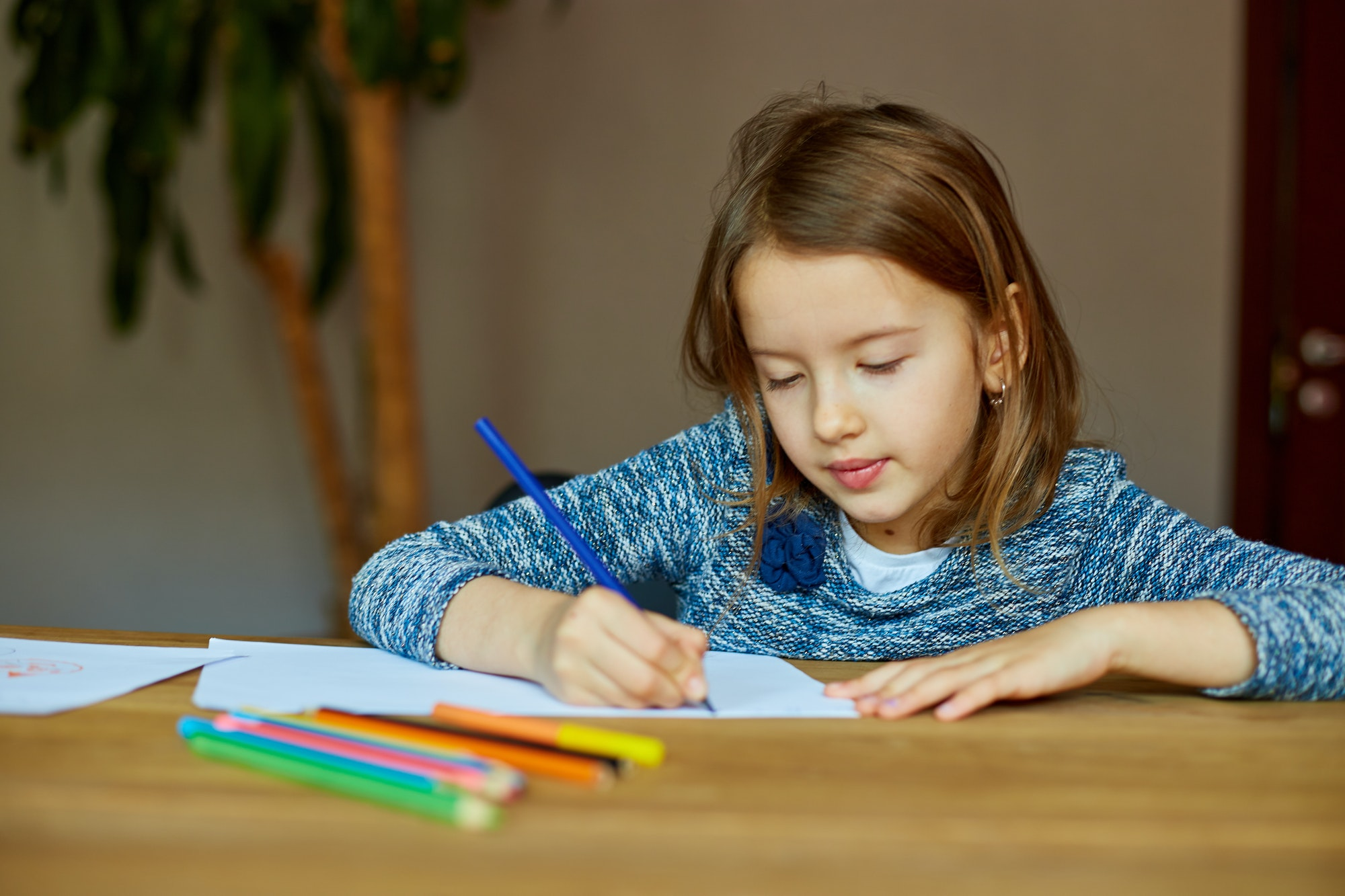School girl drawing and writing a picture with crayons, using colored pencils