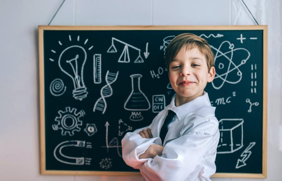 Smiling kid looking at camera in front of blackboard