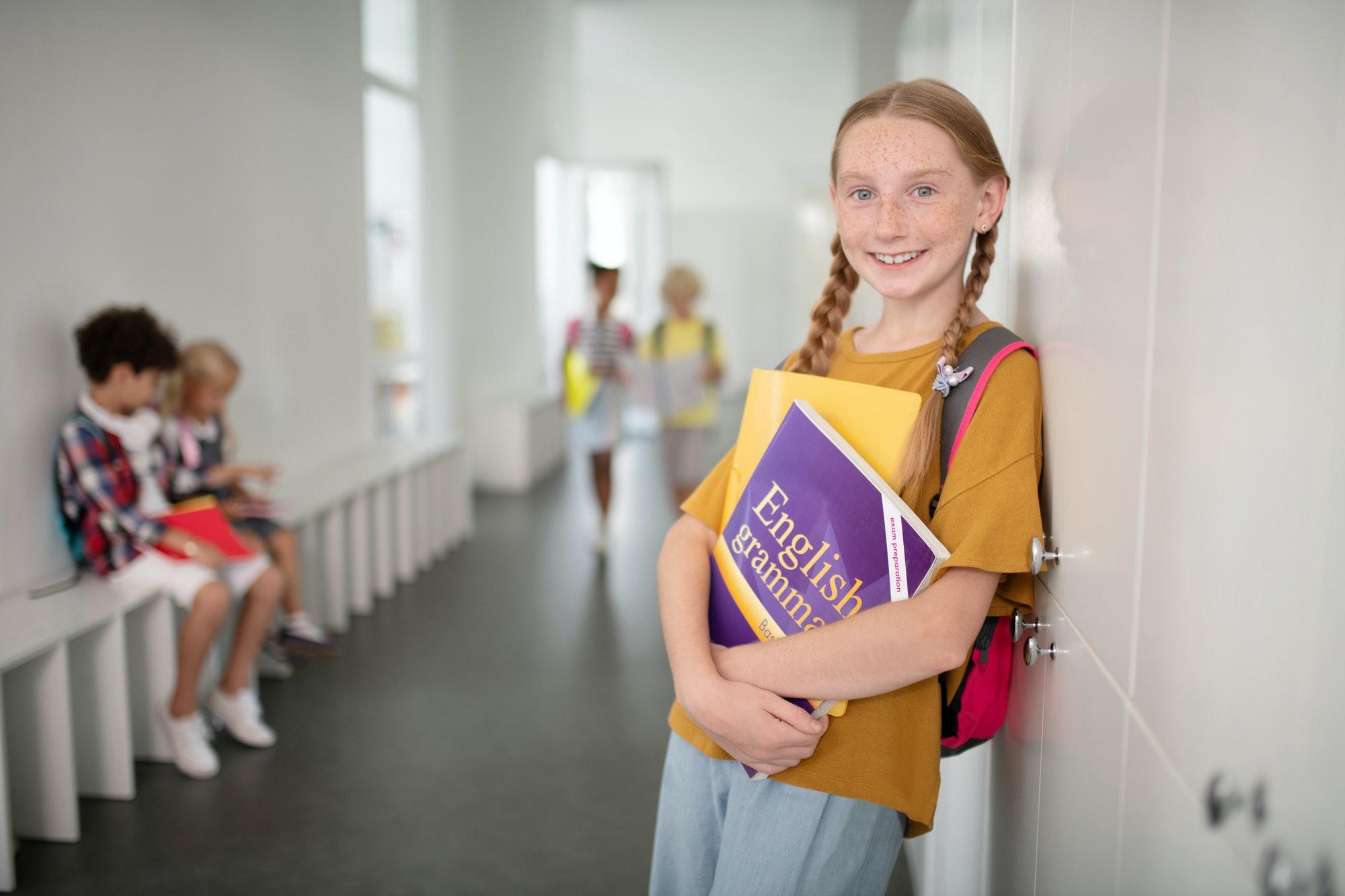 Beautiful schoolgirl holding boy while standing near locker