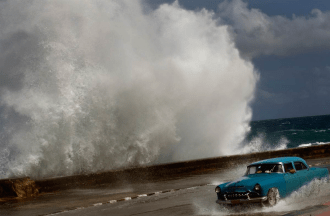 Crashing surf as a classic car seeks refuge