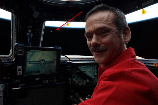 The UFO can be seen as a tiny speck through an ISS portal window