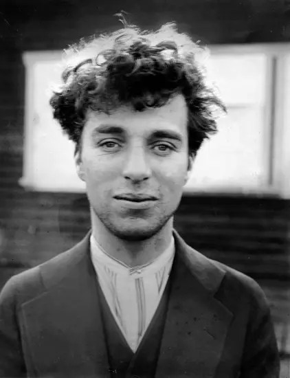 Charlie Chaplin in a photo without his makeup and classic hat.