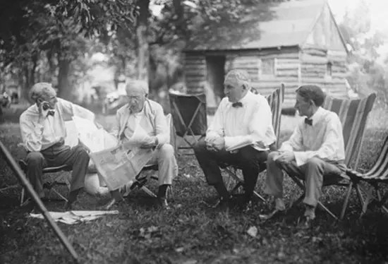 A meeting of the minds – Henry Ford, Thomas Edison, Warren G. Harding, and Harvey Firestone sitting on lawn chairs in a yard.