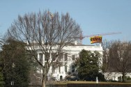RESIST banner hanging from crane behind White House