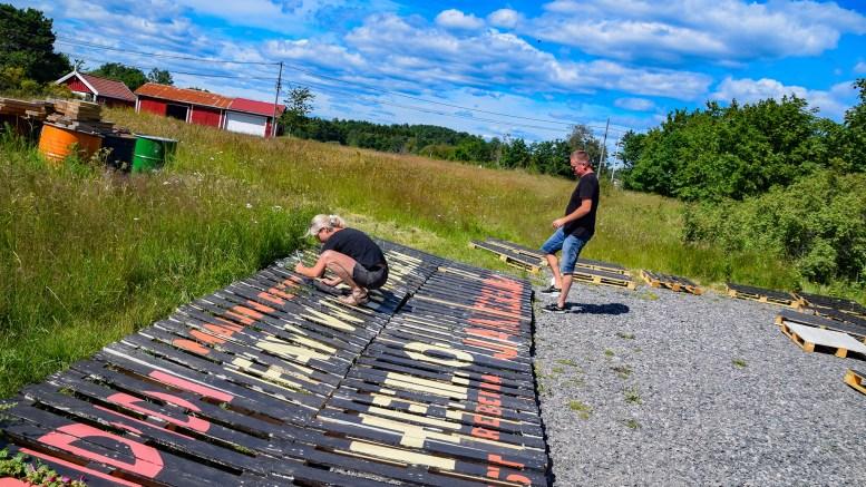 SPORNESFESTIVALEN: Mari Dale er i gang med å male festivalvegger, mens Tom Rudi Torjussen ordner til «loungene» i enga. Fredag braker det løs ved Flademoen. Foto: Esben Holm Eskelund