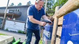 SKILTENE RYKER: Klubbleder Geir Støylen i Tromøy IL tar ned skiltene som Sparebanken Sør har sponset klubbe med. Han er overrasket over årsaken til at landsdelens største bank struper krana. Foto: Esben Holm Eskelund