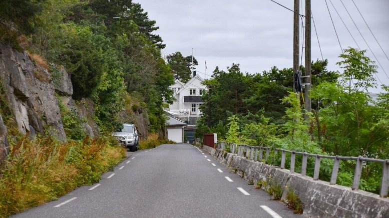 MISTET STEINBLOKK: Over veien her skal steinblokken ha falt fra Jonsvoll, som ligger på oversiden til venstre i bildet. Foto: Esben Holm Eskelund