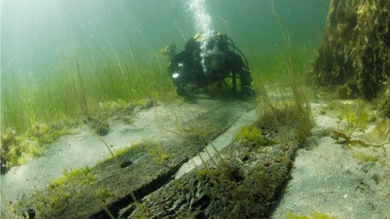 OPPSIKTSVEKKENDE FUNN: Skipsvrakrestene man trodde var fra 1700-tallet viser seg å være fra 1200-tallet. Her er dykkere nede på dypet der to skipsplank i eik er frilagt, funnet under et finkornet sandlag. Foto: Norsk Maritimt Museum / Rapport
