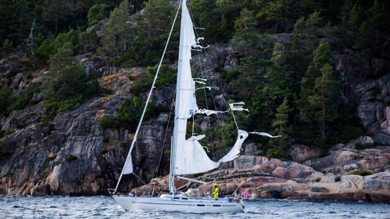 REVNET SEIL: I hardt vær i Skagerrak spjæret seilet på seilbåten, som søndag kveld ble loset i land inn Tromøysund ved hjelp av mannskap på RS Inge Steensland. Foto: Esben Holm Eskelund