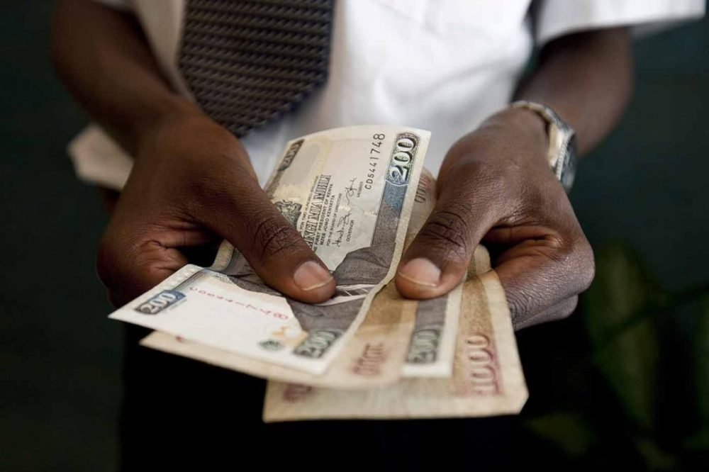 A man counts Kenyan Schillings, the currency of Kenya, in Nairobi, Kenya, on Thursday, Feb. 25, 2010. Kenya National Bureau of Statistics said it will postpone publishing February's inflation data by at least a day or two to prepare for the release of a revised consumer price index basket. Photographer: Trevor Snapp/Bloomberg