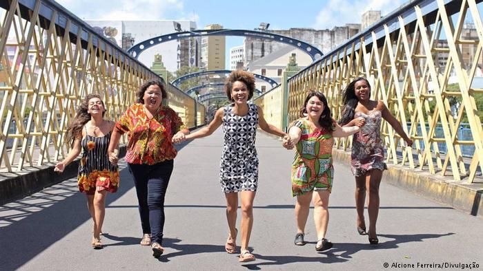 5 mulheres correndo e sorrindo em uma ponte, elas são do partido JUNTAS