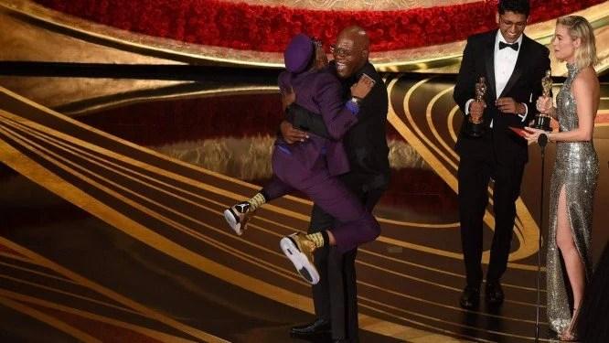 Spike Lee pula no pescoço do ator Samuel L. Jackson ao aceitar o Oscar de melhor roteiro adaptado por 'Infiltrado na Klan'