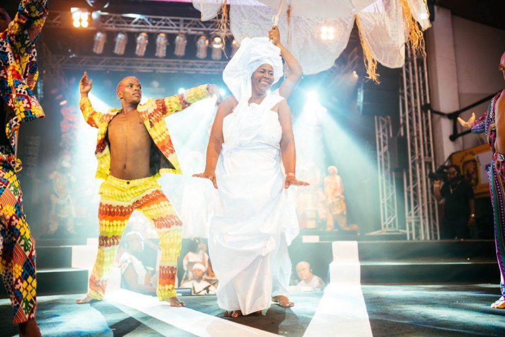 Mulher vestida de branco e homem negro no palco