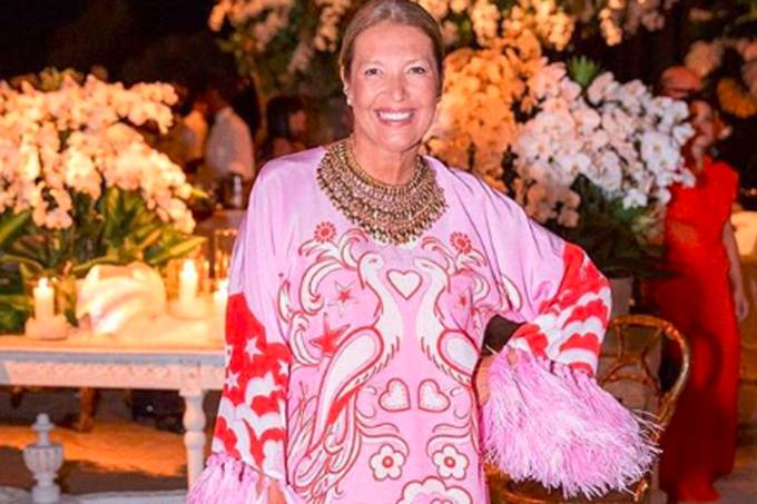 Donata Meirelles,  com um vestido rosa e estampado, canelos loiros presos e um colar. A diretora de estilo da Revista Vogue está em pé em um ambinete fechado com flores no fundo