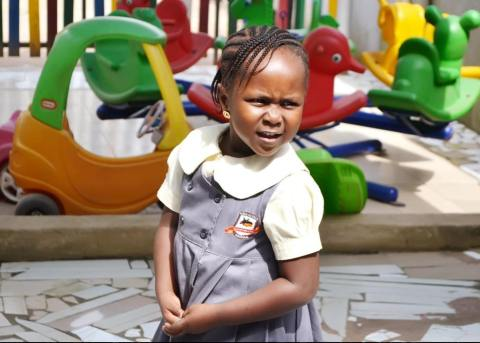 Criança negra de aproximadamente três anos em ambiente escolar