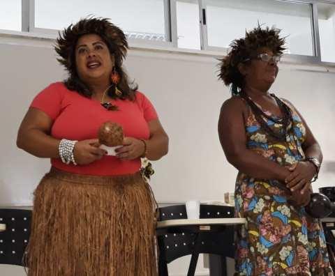 Cláudia Silva Barbosa e dona Maria da Glória de Jesus - mulher negra- em pé durante um discurso