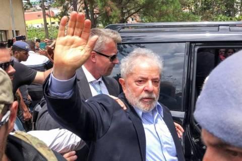 Luiz Inácio Lula da Silva, homem idoso branco, em pé acenando para uma multidão antes de entrar em um carro preto.