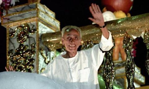 Betinho, homem idoso branco, durante o desfile da Império acenando para o publico em cima de um carro alegórico